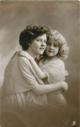 mother & girl in filmy dress have arms round each other, both face & look front