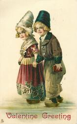 Dutch boy & girl stand holding hands, he has book in other hand