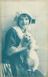 seated Dutch girl facing right, looking front, cuddles white cat held sitting up on her lap