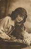 pretty girl in floppy bonnet leans over pekingese dog on cushion on a table, girl  faces & looks front has left hand under dogs chin