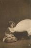 young girl sits undressed on cushion to left of portable bath tub