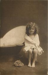 young girl sits wrapped in towel on stool to right of portable bath tub