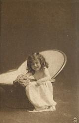 young girl sits in portable bath tub, facing left & looking forward, sponge to left