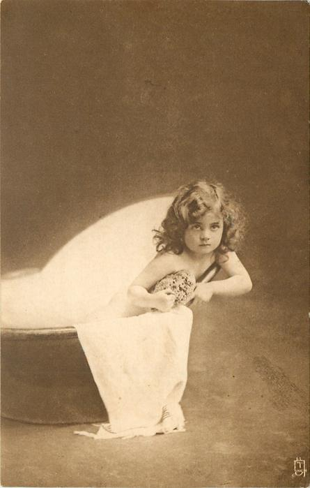 young girl sits in portable bath tub, facing forward, sponge directly in front held with both hands, left arm outside tub