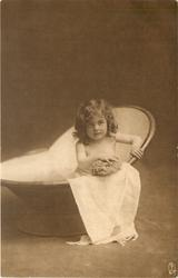 young girl sits far to right in portable bath tub, facing  forward, looking up, sponge directly in front held with right hand