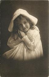 young girl in bonnet  & dress sits facing & looking front, hands touching in front under tie