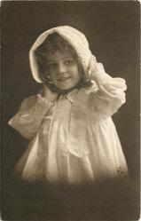 young girl in bonnet  & dress sits facing half left, looking front, right hand under her chin, left hand on bonnet