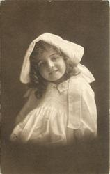 young girl in bonnet & dress sits facing half left, looking front, arms at sides