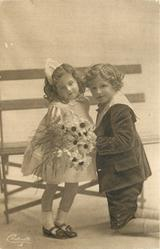 young children in front of openwork wooden seat, girl stands in front, boy kneels on ground offering flowers