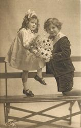 young children on openwork wooden seat, girl sits on back, boy kneels offering flowers