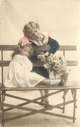young children on openwork wooden seat, girl sits with legs extended to right, boy hangs over back offering flowers