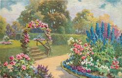 blue delphiniums & roses to right of path leading up steps under floral arch, hedge & trees behind