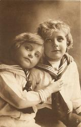 two children in sailor suits, child left rests head on other's shoulder & holds his necktie, both look up/left
