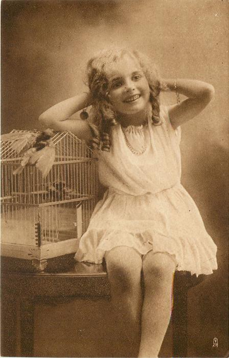 girl sits on table to right of bird cage with stuffed bird perched on top, hands at her head
