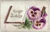 A HAPPY BIRTHDAY  pansies lie on open book
