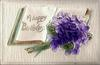 A HAPPY BIRTHDAY  violets lie on open book
