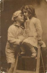 young children & wooden step-ladder, girl sits at top looking forward, boy stands below to left looking forward, her right hand round his neck, his right hand held on her lap