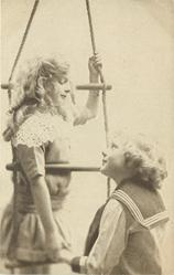 boy looks up at girl on rope ladder