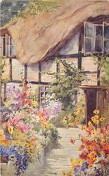 stone path, between masses of flowers on each side, leads up to door of thatched cottage