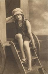 girl in bathing suit & cap sits on top step of bathing hut, her left arm hangs down, her right hand behind her neck