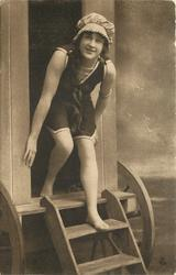 girl in bathing suit & cap stands at front of bathing hut, her hands hold sides of doorway, her right foot is inside hut, left foot on step