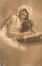 girl with frilly cap left of pekingese dog on pillow which faces front, girl looks up to left