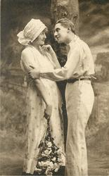 two lovers stand in front of tree trunk, he holds her right arm with his left hand, floral bouquet hangs down