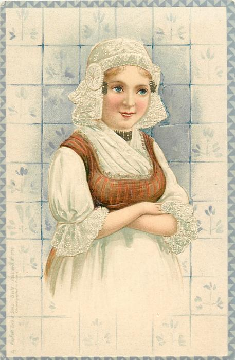 woman facing front stands with arms folded, delft tiles behind