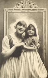 mother & child in Dutch costume stand in front of framed mirror, both facing front , mothers left hand on girls left arm, girls left hand holds mothers right