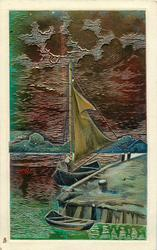 very shiny, metallic painted card with sailing boat & dingy tied up to warf, golden brown sky  & water