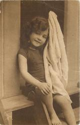 young girl in bathing costume in door of bathing hut, she sits in door holding towel up with her left arm