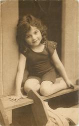 young girl in bathing costume in door of bathing hut, she sits in door with legs folded under her, right arm forward