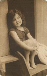 young girl in bathing costume sitting in door of bathing hut, arms joined around her knees