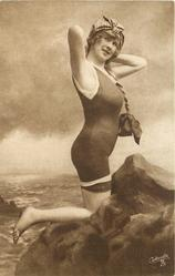 girl in bathing suit & hat kneels on rocks, braid hangs on her left, hands behind neck, faces right & looks forward