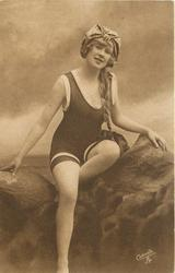 girl in bathing suit & hat sits on rocks, left leg tucked up, braid hangs on her left, looks & faces forward