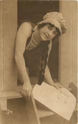 girl in bathing suit  & cap sits in door of bathing hut looking out, she holds paper in her left hand