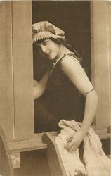 girl in bathing suit  & cap sits in door of bathing hut, she sits facing left, holds towel with left hand