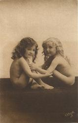two little girls, both sit with knees up