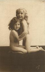 two little girls, blond girl kneels right, they embrace
