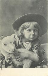 child cuddling and leaning over toy lamb, left arm and right hand visible