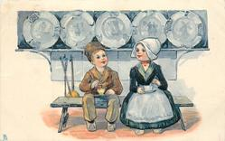 Dutch boy and girl sitting with tea, ornamental plates at back above