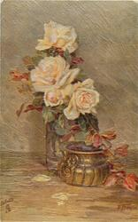 four cream roses in clear vase, a gold pot in front, several petals on table