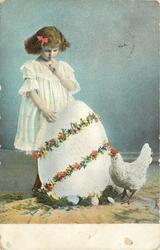 small girl with finger to lips, large egg, hen on ground