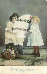 two young girls hold large egg, basket of flowers on ground