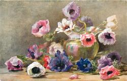 bluish green vase surrounded by anemones lying on the ground, in the vase the flowers are pink, white and purple