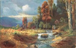two people walk on right side of of rushing stream with waterfalls, large trees right, tall grass left