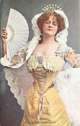 standing in yellow gown, long white lace shawl, fan in her right hand, dress ties down front