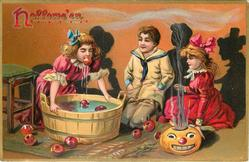 girl bobs for apples over tub, boy and girl look on, jack o lantern lower right