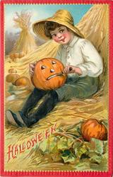 child sitting in hay carving mouth of jack o lantern