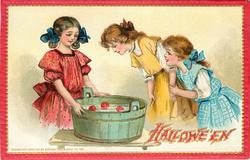 three girls around tub of water and apples